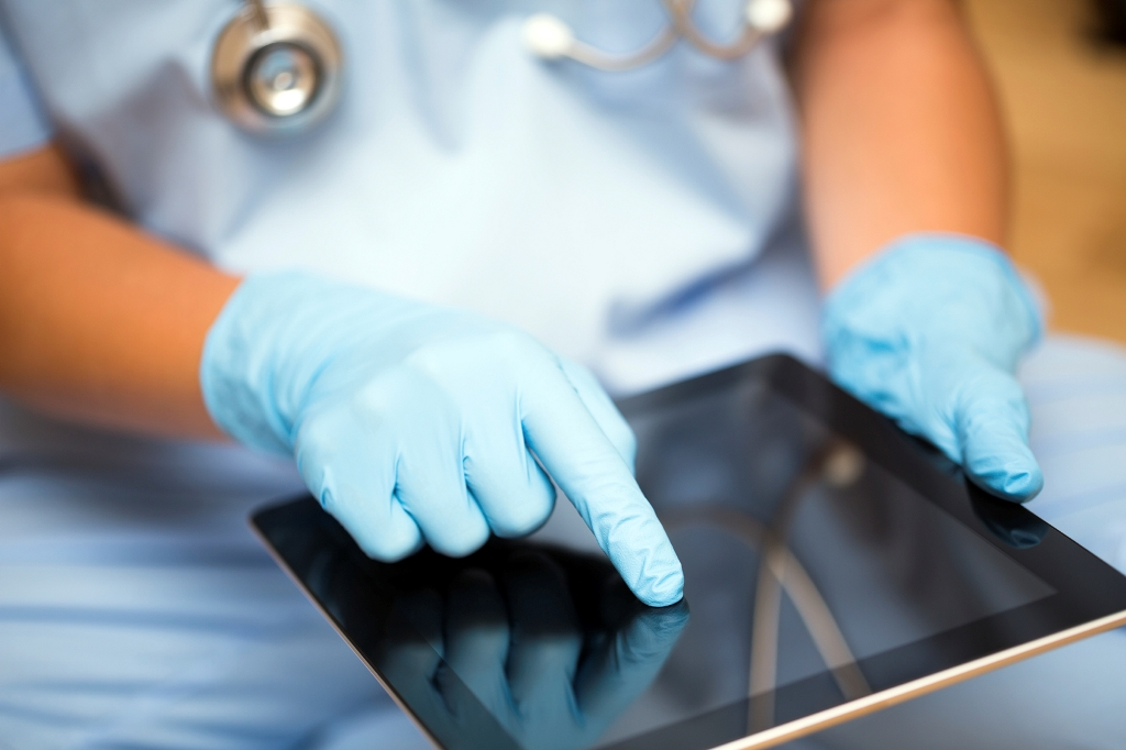 Doctor with gloves using Ipad